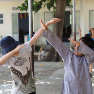 two young boys aged ten, one in a dinosaur t-shirt the other in buddhist robes, dabbing