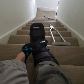 Image of two feet on stairs, the left one in a short sock with blue stars, the right in a moon boot. The photo is taken from the top of a staircase looking down. There is a pair of crutches lying halfway down the stairs.