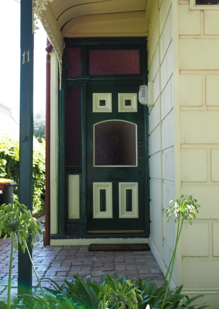Front door to a house that is inset with windows in a configuration that makes it look like it is screaming sadly